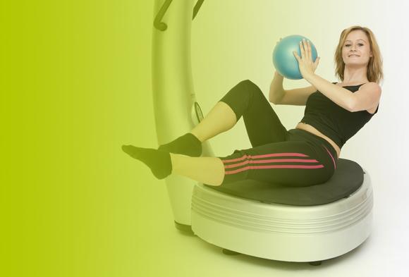 Frau mit Ball auf Vibrationsplatte